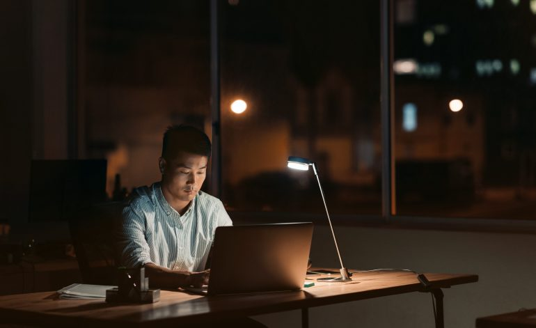 Decorative image of a man working at his desk with a lamp on